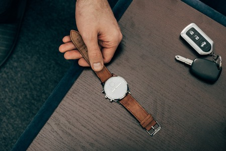 cropped image of businessman taking off watch from table at home 写真素材 - 111788934