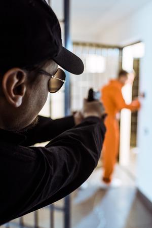 prison guard aiming gun at prisoner Banco de Imagens