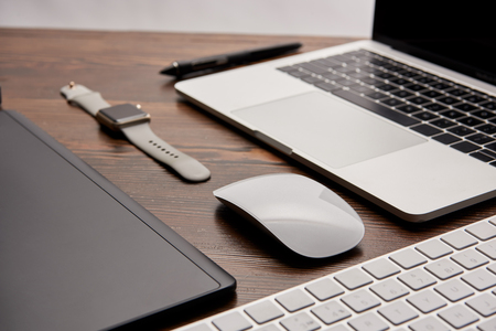 close-up shot of laptop with wireless mouse and keyboard lying on wooden table with smart watch and graphics tablet Stock Photo