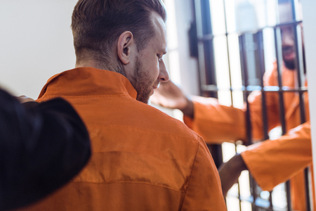 cropped image of prison guard leading criminal Stock Photo