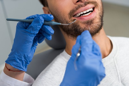 cropped shot of female dentist examining teeth of happy client