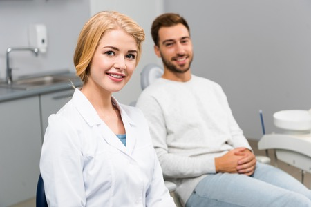 smiling female dentist and handsome young client looking at camera in dentist office 写真素材