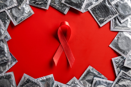 top view of aids awareness red ribbon and silver condoms on red background Stockfoto