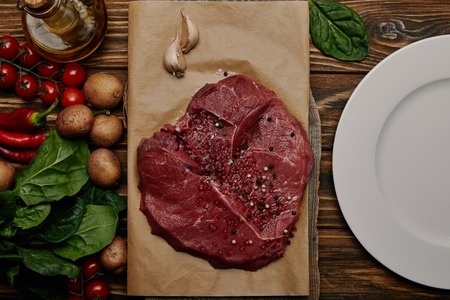 flat lay with fresh raw meat on baking paper with vegetables and spinach on wooden background
