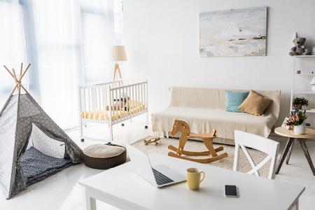 modern interior design of nursery room with baby wigwam and crib
