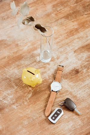 high angle view of remote car key, watch, piggy bank and branch at wooden table