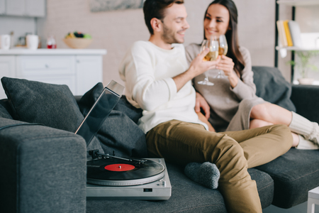 happy young couple listening music with vinyl record player and drinking wine at home 免版税图像
