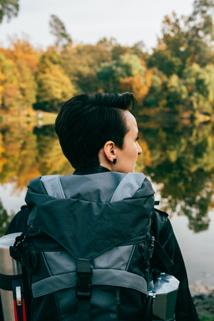 female traveller with backpack on autumnal background