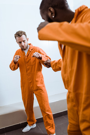 multicultural prisoners fighting in prison room Stock Photo