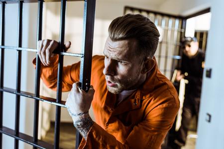 Scared prisoner leaning on prison bars