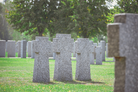 selective focus of identical old gravestones placed in row on grass at cemetery