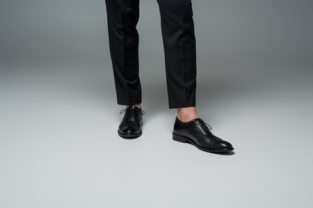 Partial view of stylish male legs in black formal shoes on grey Stock Photo