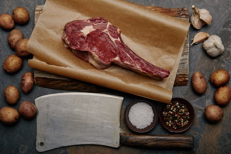 flat lay with raw rib eye steak on baking paper with butcher knife, spices, potatoes and garlic