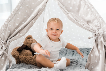 smiling adorable toddler sitting in baby wigwam with fluffy teddy bear toy