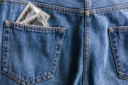 pair of silver condoms in pocket of blue jeans