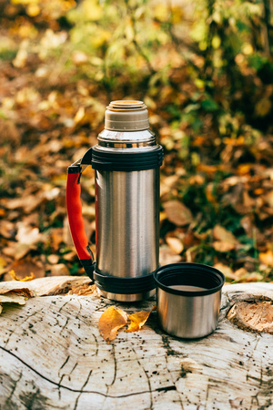 metallic camping thermos on beautiful autumnal background Stock fotó