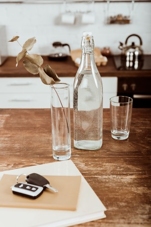 close up view of remote car key, bottle of water and branch in vase at wooden table in kitchen