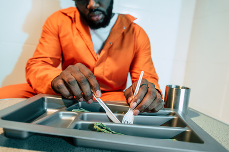 cropped image of african american prisoner eating in prison cell
