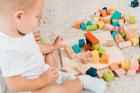side view on adorable toddler playing with colorful cubes