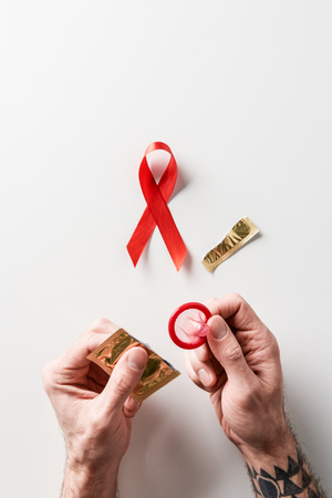 male hands holding golden packaging and red condom with aids awareness red ribbon on white background
