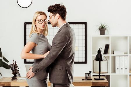 młodzi prawnicy przytulają się, stojąc w biurze, flirt i koncepcja romansu w biurze
