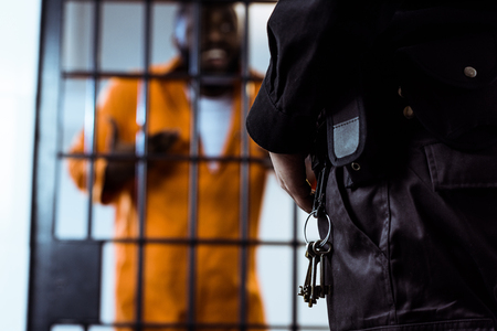 cropped image of security guard standing near prison bars with keys
