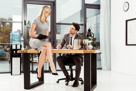 lawyer looking at beautiful female colleague on table in office, office romance concept