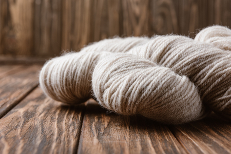 close up view of white yarn for knitting on wooden surface