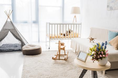 Modern interior design of nursing room with crib and baby wigwam