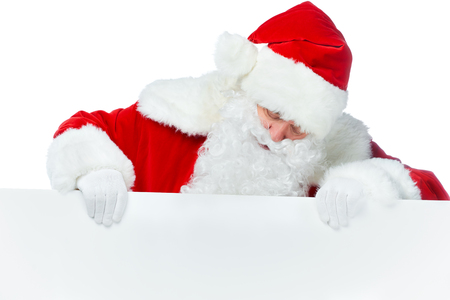 Bearded Santa Claus looking at empty board isolated on white