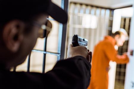 Prison officer aiming gun at escaping prisoner