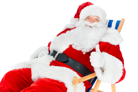 Bearded Santa Claus showing thumb up and sitting in beach chair isolated on white