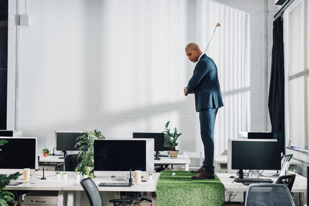 Side view of young African american businessman playing golf on table in office