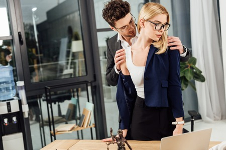 Businessman undressing businesswoman at workplace in office Stok Fotoğraf