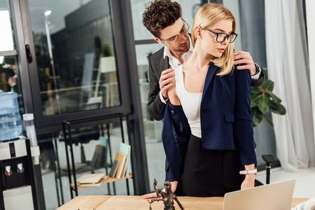 Businessman undressing businesswoman at workplace in office Zdjęcie Seryjne