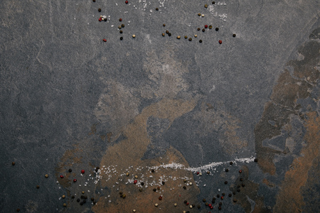 Top view of scattered salt and allspice on grey marble background