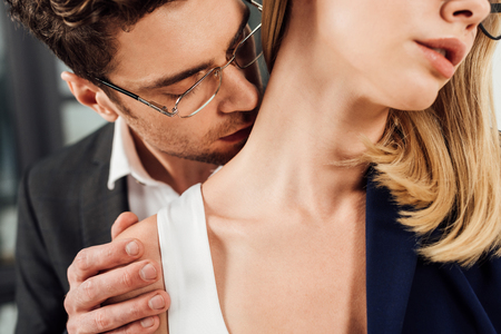 Partial view of businessman kissing colleagues neck, office romance concept