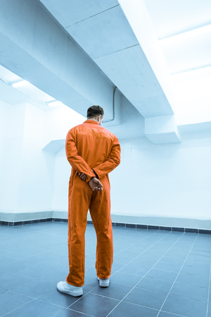 Rear view of prisoner in orange uniform standing in prison cell