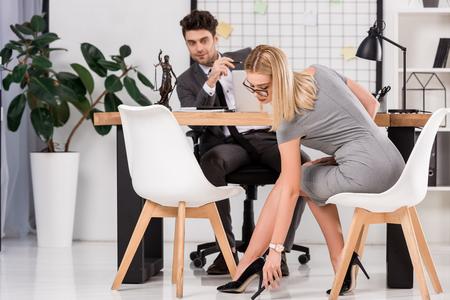 Joven empresaria coqueteando con un colega de negocios en el lugar de trabajo con un portátil en la oficina