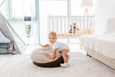 Adorable toddler in white nursery room