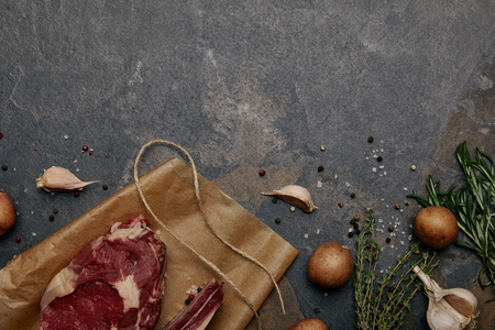 top view of raw meat steak on baking paper with spices, herbs and potatoes on grey background
