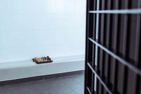empty prison cell with chessboard on bench