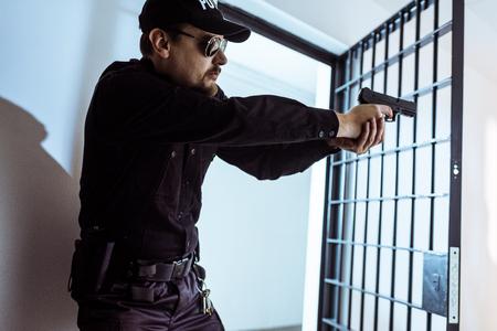 prison guard aiming gun and looking away