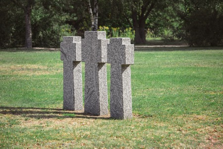 scenic view of identical old gravestones on grass at graveyard Stockfoto