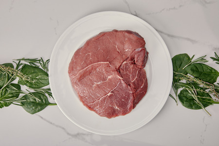 top view of fresh raw meat on plate with herbs on white background