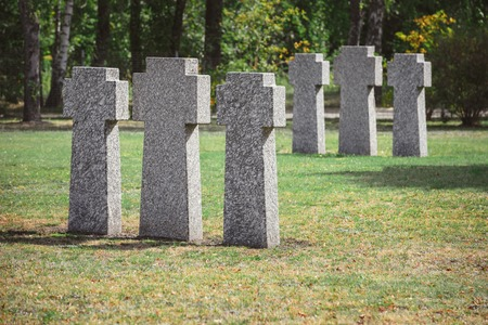 selective focus of identical gravestones placed in rows at graveyard