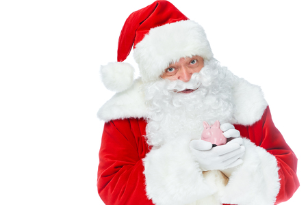 santa claus holding little piggy bank and looking at camera isolated on white
