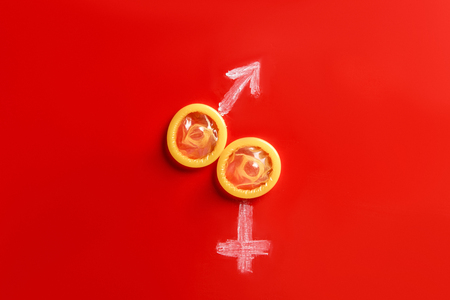 top view of condoms with male and female signs on red background Stockfoto