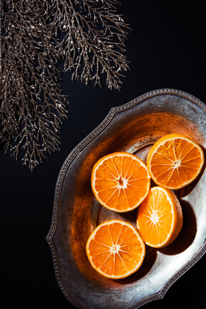 flat lay with mandarins in metal bowl and decorative silver twig on black backdrop