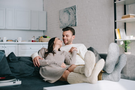 happy couple in woolen socks relaxing on couch at home Stockfoto
